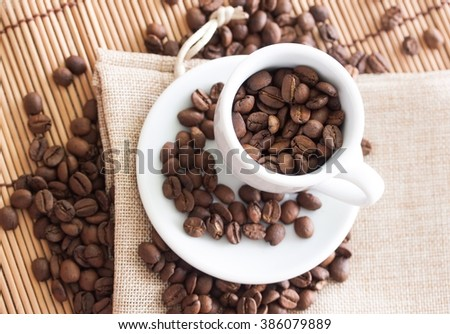 Coffee beans in mug on linen bag and bamboo mat