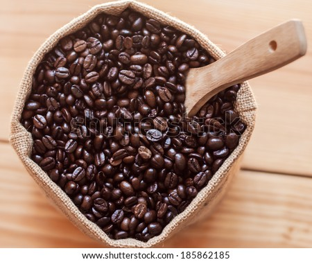 Coffee beans in sack with wooden scoop on top view - stock photo