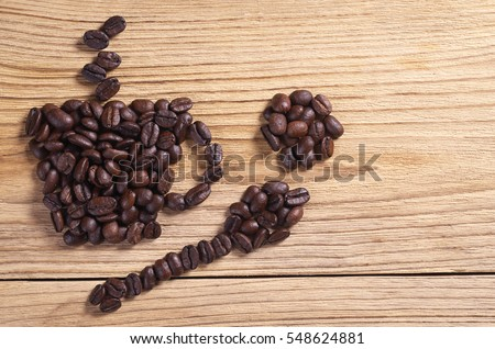 Coffee beans in shape of cup, spoon on wooden table, top view