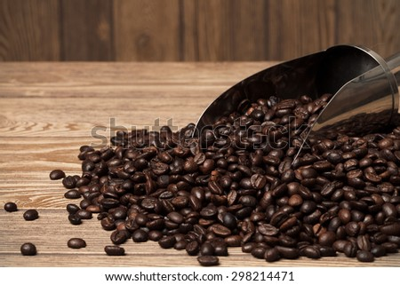 Coffee beans in spoon on wooden table. Space for text.