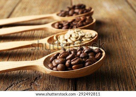 Coffee beans in spoons on wooden background - stock photo