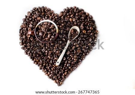 Coffee beans in the shape of a big heart with mug & spoon - stock photo