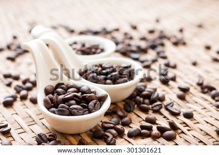 Coffee Beans in white spoon on wooden background - stock photo
