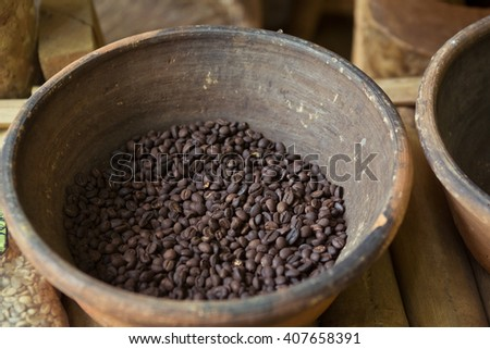 Coffee beans in wooden bowl on wooden background. Selective focus. - stock photo