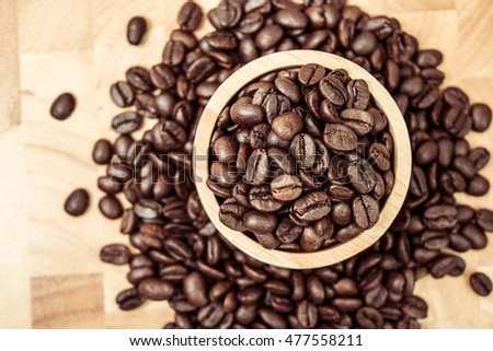 Coffee beans in wooden bowl on wooden background, top view