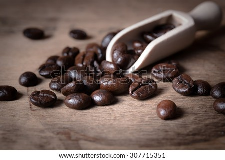 Coffee beans in wooden scoop - stock photo