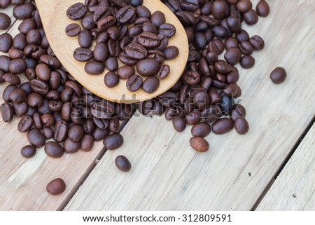 Coffee beans in wooden spoon close up