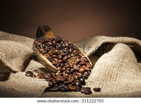 Coffee beans in wooden spoon on burlap textile background. - stock photo