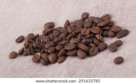 Coffee beans isolated on tissue background - stock photo
