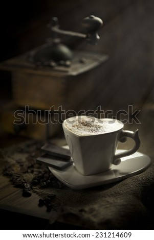 Coffee beans jute background with coffee grinder and hot cup of coffee on wooden table  - stock photo