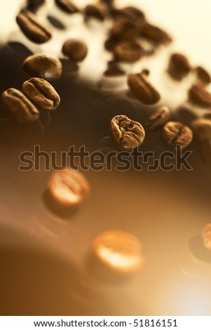 Coffee beans lying on a shiny glass surface. - stock photo