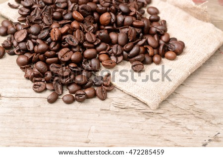 Coffee beans on a rustic wooden background with sackcloth