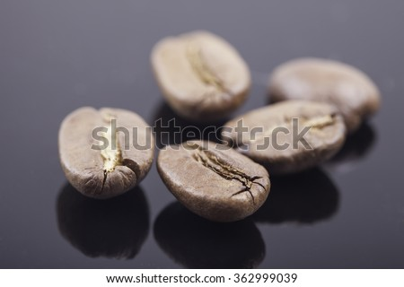 Coffee beans on a shiny black surface closeup macro - stock photo