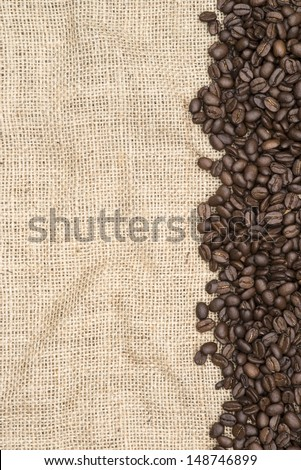 Coffee beans on hessian background as a border - stock photo