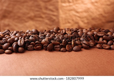 Coffee beans on table on brown background - stock photo
