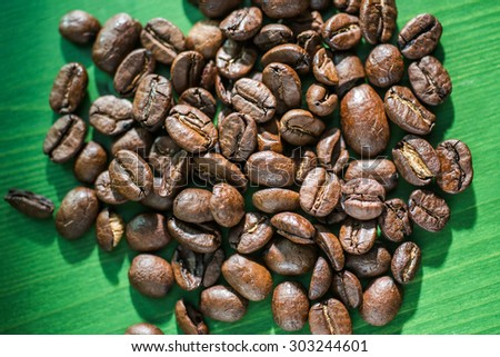 Coffee beans over a green background