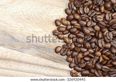 coffee beans scattered on wood board background texture