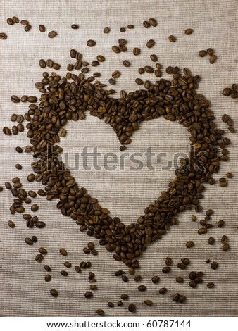 Coffee beans spilled on natural background, shaped as a heart. - stock photo