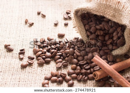 Coffee beans spilled out of the bag on the fabric in the photo have 2 sticks of cinnamon and anise. Cinnamon is an angle of 45 degrees to the center of the frame. part of the photo is not in the field - stock photo