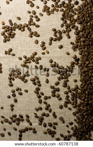Coffee beans spilled over a natural background. - stock photo