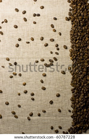 Coffee beans spilled over a natural background forming a frame on one side of the image. - stock photo