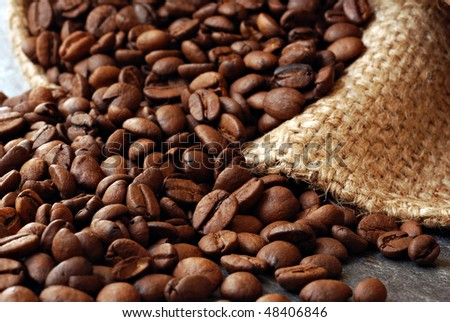 Coffee beans spilling from burlap sack onto slate counter. Macro with extremely shallow dof. - stock photo