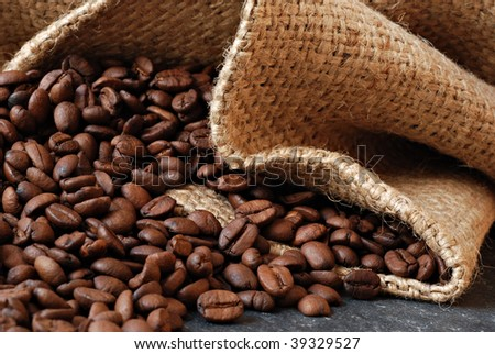 Coffee beans spilling from burlap sack onto slate counter.  Macro with shallow dof. - stock photo
