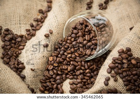 Coffee beans spilling from glass cup