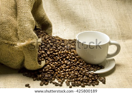 Coffee beans spilling out around coffee cup and saucer/ Coffee Beans Spilling Out And Coffee Cup - stock photo