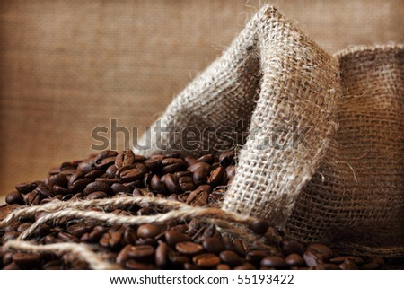 Coffee beans spilling out from a burlap sack - stock photo