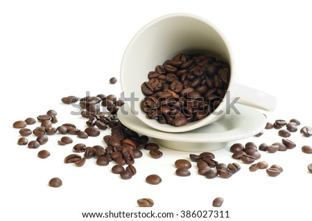 Coffee beans spilling out from a coffee cup, isolated on white background.