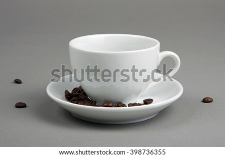 Coffee beans spilling out from a coffee cup on gray background - stock photo