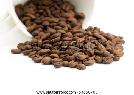Coffee beans spilling out from a cup - stock photo