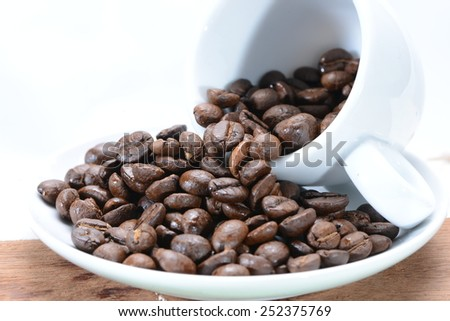 Coffee beans spilling out of a coffee cup - stock photo