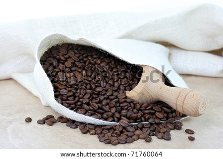 Coffee beans spilling out of a cream colored burlap sack.  Coffee scoop inside sack. - stock photo