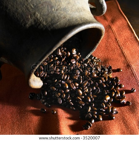 Coffee beans spilling out of an old pottery jug