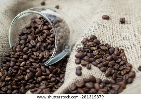 Coffee beans spilling out of glass cup - stock photo