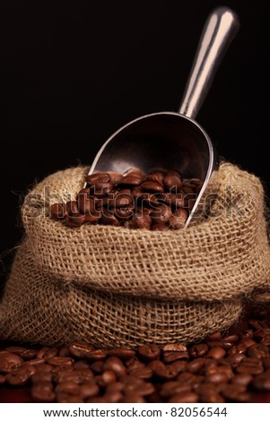 coffee beans spilling out of steel scoop - stock photo