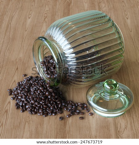 Coffee beans spilling out vintage glass jar on wooden surface  - stock photo