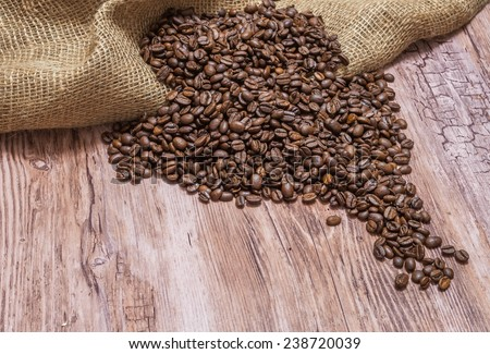 Coffee beans strewn on wooden table - stock photo