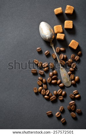 coffee beans, sugar and silver spoon on black background - stock photo