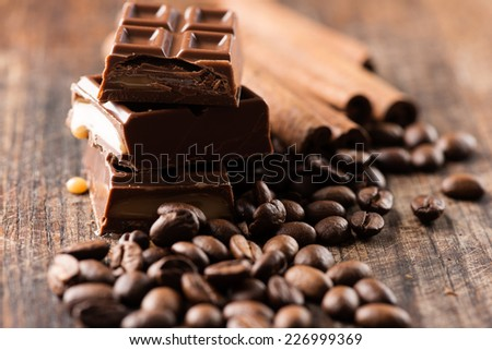 Coffee beans with chocolate bar on wooden table - stock photo