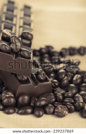 Coffee beans with chocolate glaze and dark chocolate on grey tablecloth - stock photo