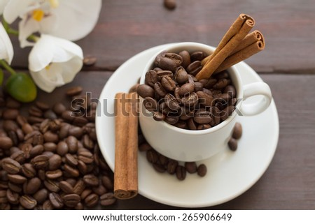 Coffee beans with cinnamon and orchid flowers - stock photo