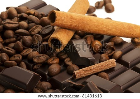 coffee beans with cinnamon sticks and chocolate pieces on a chocolate bar - stock photo