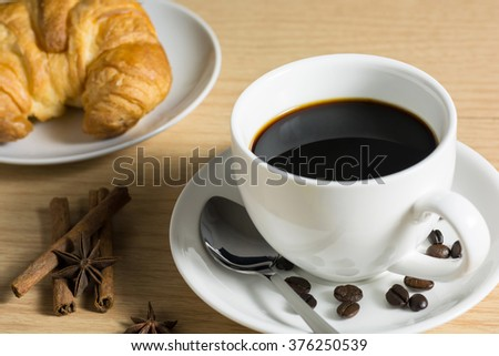 Coffee beans with coffee black in white cup and cinnamon stick with star anise spice in wooden background. Still Life. - stock photo
