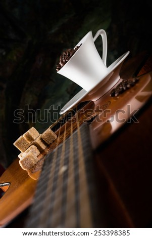 coffee beans with  coffee cup and cane sugar on a guitar