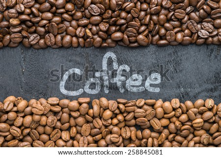 Coffee beans with Coffee hand writing  on black wooden background with blank space. - stock photo