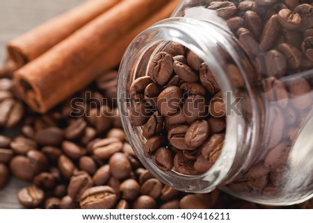 Coffee beans with glass jar and cinnamon, closeup macro shot, selective focus - stock photo