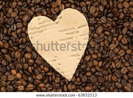coffee beans with heart shaped piece of cardboard in the middle